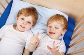 stock photo of baby twins  - Family of two little boys: Twins having fun in bed at home indoors. ** Note: Shallow depth of field - JPG