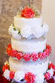 stock photo of three tier  - Beautiful wedding cake in different colors with three levels and marzipan roses - JPG