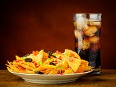 stock photo of nachos  - nachos on a plate served with a glass of cold cola drink - JPG