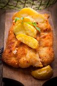stock photo of cod  - Fried fillet of cod with french fries on a wooden board - JPG