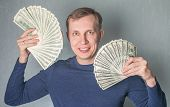 picture of greedy  - greedy man Displaying a Spread of dollars Cash - JPG