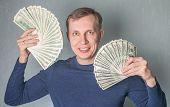 foto of greedy  - greedy man Displaying a Spread of dollars Cash - JPG