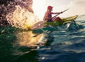 foto of kayak  - Young lady paddling hard the sea kayak with lots of splashes - JPG