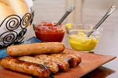 picture of condiment  - Grilled brats on a stacked on a plate ready to serve with condiments ketchup and mustard and buns - JPG