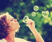 stock photo of blowing  - a beautiful woman blowing bubbles  - JPG