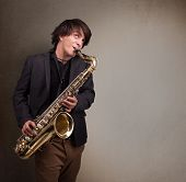 picture of saxophone player  - Handsome young musician playing on saxophone - JPG
