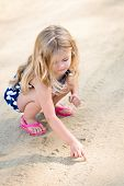 picture of squat  - Cute thoughtful little girl with long blond hair squatting and drawing in the sand on the beach in summer day - JPG
