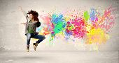 picture of jumping  - Happy teenager jumping with colorful ink splatter on urban background concept - JPG