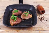 stock photo of bloody  - fresh grilled bloody beef steaks on black grill plate on wood - JPG