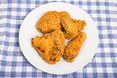 picture of southern fried chicken  - Four pieces of fresh fried chicken on a plate and blue plaid towel - JPG