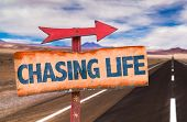 stock photo of chase  - Chasing Life sign with road background - JPG