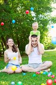 stock photo of mums  - Happy family outdoors mum and dad hold baby playing with colorful balls sitting on grass - JPG