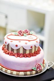 picture of icing  - Beautiful wedding cake in different colors with two levels and marzipan roses. Icing with cream marzipan details of cake.