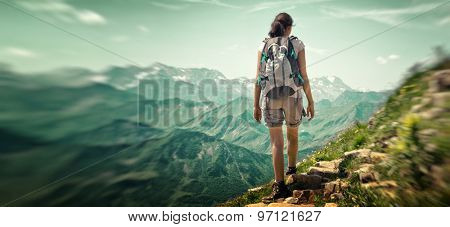 Woman hiking in mountain range. Rear view of a female backpacker walking on a small foot path in a m