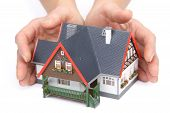 picture of real-estate agent  - Female hands with model of house on a white background - JPG