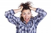 stock photo of frazzled  - A woman is very frazzled with her hands in her hair - JPG