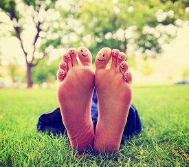 image of painted toes  -  smiley faces on a pair of feet on all ten toes in a park setting toned with a retro vintage instagram filter app or action effect  - JPG