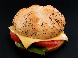 stock photo of veggie burger  - Veggie Burger with cheese and tomatoes isolated on black background - JPG