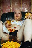 foto of couch potato  - Photo of a fat couch potato eating a huge hamburger and watching television - JPG