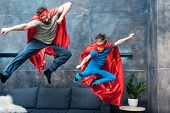 Father And Son In Superhero Costumes Jumping On Sofa At Home poster