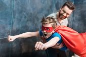 Father Holding Son In Superhero Costume Flying At Home poster