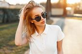 Beautiful Young Woman In Sunglasses And A White Polo Shirt Walking At Sunset poster
