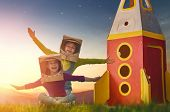 Children in astronauts costumes with toy rocket playing and dreaming of becoming a spacemen. Portrai poster