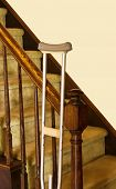 picture of bannister  - Crutch leans against bannister of stairs with plain wall behind providing copy space - JPG