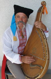 picture of musical instrument string  - Senior ukrainian folk travelling musician bandurist named Kobzar with instrument bandura - JPG