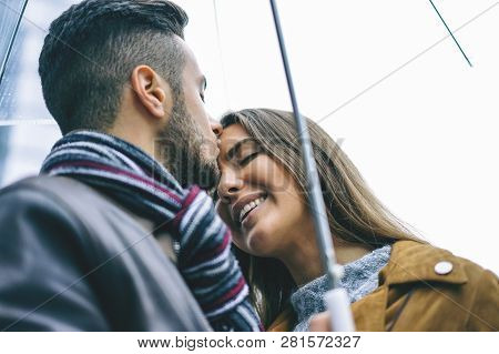 poster of Happy Couple Kissing Under An Umbrella In A Rainy Day - Handsome Man Kiss His Forehead Girlfriend Un