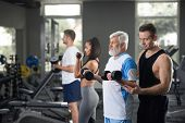Indoor Portrait Of People During Daily Training In Gym. Elderly Man Keeping Fit And Training With We poster