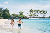 Fun beach summer vacation couple running together happy. Hawaii beach island travel holiday. Asian w poster
