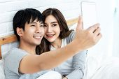 Young Asian Couple Lying On Bed And Taking Selfie By Smartphone. Asian Lovers Take A Photo With Toot poster