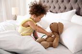 Cute African American Child Imagining Herself As Doctor While Playing With Stethoscope And Toy Bunny poster
