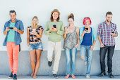 Young People Watching On Their Smart Mobile Phones Leaning On A Wall - Generation Addicted To New Te poster