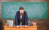 Teacher Strict Serious Bearded Man Lean On Table Chalkboard Background. Teacher Looks Threatening. S poster