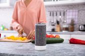 Close-up Of A Woman Working In Kitchen With Smart Speaker In Foreground poster