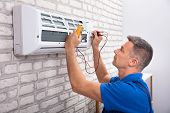 Male Electrician Checking Air Conditioner With Digital Multimeter poster