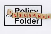 stock photo of scrabble  - Your insurance policy folder with wood scrabble in white background - JPG