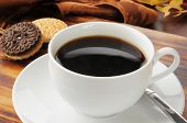 foto of duplex  - A cup of black coffee with duplex sandwich cookies