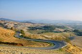 stock photo of long winding road  - Winding road in brown autumn coloursTuscany Italy - JPG