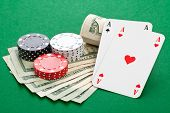 stock photo of ace spades  - Casino chips with pocket aces on dollar bills on poker table - JPG
