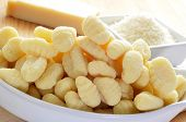 image of grating  - closeup of a pile of gnocchi and a bowl with grated parmesan cheese - JPG