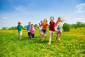 stock photo of dandelion  - Large group of kids running in the dandelion spring field - JPG