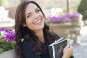 foto of degree  - Portrait  of Pretty Young Female Student Carrying Books on School Campus - JPG