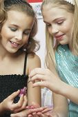 stock photo of slumber party  - Closeup of a young girl applying nail polish to friend - JPG