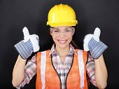 Construction worker happy woman doing thumbs up with protection wear. Young woman wearing safety gla