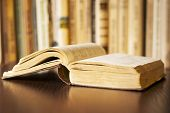 picture of splayed  - open book on the table and a bookshelf in the background - JPG