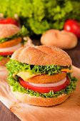 stock photo of baps  - Fresh fishburger sandwich on the table. Selective focus in the middle of fishburger ** Note: Shallow depth of field - JPG