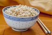 image of chopsticks  - Brown rice served in a Chinese blue and white rice pattern bowl - JPG